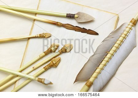 Primitive hunting and fishing arrows with flint stone wood and bone arrowheads over aged paper sheets