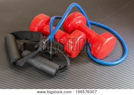 Red dumbbell weights and resistance bands lying on a black open yoga exercise mat