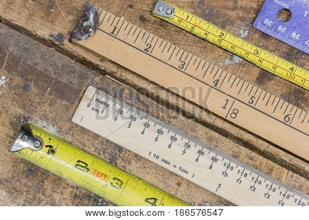 Closeup of various measuring sticks rulers tape measures layed out on scratched workshop table