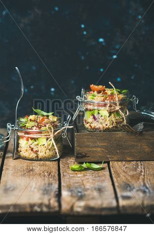 Homemade jar quinoa salad with cherry tomatoes, sun-dried tomatoes, avocado and basil. Detox, dieting, vegetarian, vegan, clean eating food concept. Dark blue background, selective focus, copy space