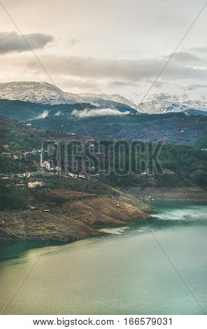 Landscape with Dim Cay storage pond and mountains covered with snow in Alanya, Southern Turkey