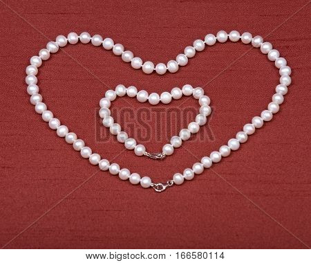 Freshwater white pearl necklace hearth shape on red fabric background