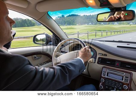 Businessman talking on cell phone while driving and overtaking, not paying attention to the road and traffic.