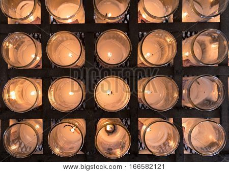 Pattern of votive candles in glass jars for prayer and remembrance in Catholic church