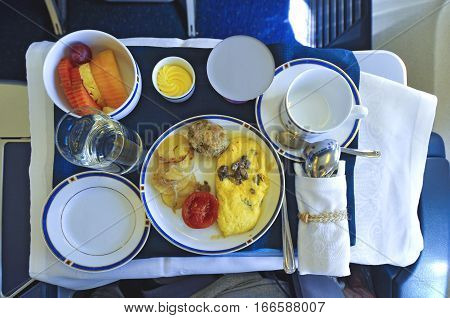 Breakfast meal with omelet and fruit on airline travelling.