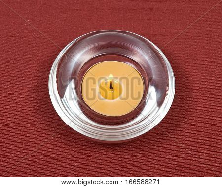 Burning yellow beeswax candle in quartz crystal bowl on red fabric background