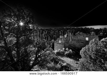 A dramatic turn of the century style photograph of Cutthroat Castle in Hovenweep National Monument. A striking view of the ancient building with early morning sunlight lighting the interior. A dark moody photograph.