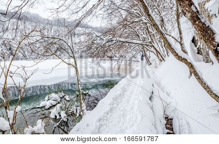 Walking trail in snowy winter at Plitvice lakes in Croatia.