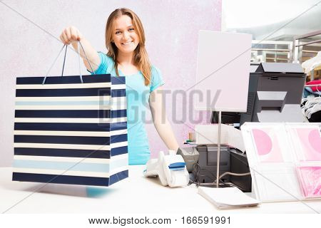 Shot of salesperson standing at cash register in fashion store