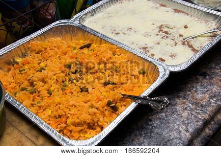 Spanish rice and cheesy refried beans in serving containers on a counter