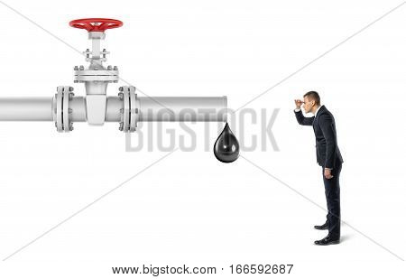 Businessman on white background looking at pipe with a red valve that's leaking one big drop of oil. Oil and gas industry. Commodities trade. Business and success.