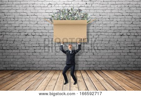 Small businessman standing on floorboard and holding a large carton box full of USD bills on grey brick background. Business and success. Burden of money. Spending and investing funds.