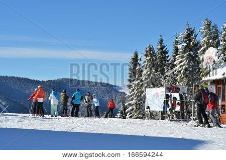 BUKOVEL, UKRAINE - December 2, 2016: Skiers on top of mountain on ski slope. Bukovel is the most popular ski resort in Ukraine.