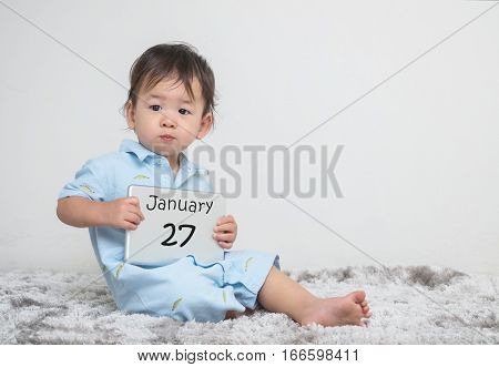 Closeup cute asian kid show calendar on plate in his hand in january 27 word on gray carpet and white cement wall textured background with copy space