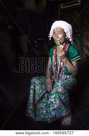 Chin region Myanmar November 11 2014: muun tribe chin lady smoking a pipe in her kitchen