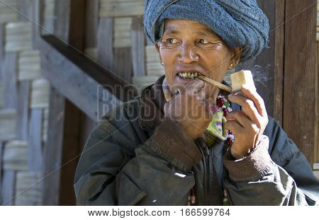 Chin region Myanmar November 11 2014: chin woman smoking a pipe outside her house