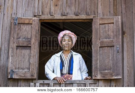 Chin region Myanmar November 11 2014: muun tribe chin lady looking out of the window