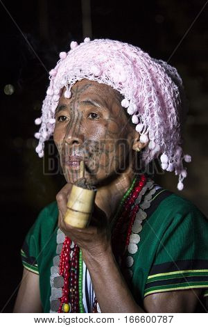 Chin region Myanmar November 11 2014: muun tribe chin lady smoking a pipe