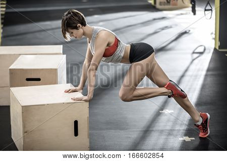 Beautiful girl leans on the wooden box with her hands and holds the left leg bent in the knee in the gym. She wears a black shorts, red top and sneakers, gray sleeveless. Horizontal.