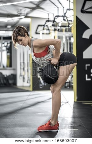 Wonderful girl with a load does a forward tilt in the gym. She wears a black shorts, red top and sneakers, gray sleeveless. Shoot from the side. Vertical.