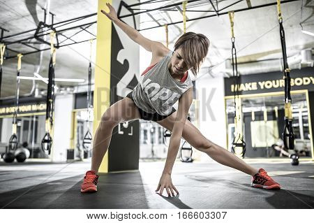 Sportive girl with parted lips does stretching in the gym on the background of the hanging TRX straps. She wears a red top and sneakers, gray sleeveless, black shorts. Horizontal.