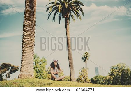 Woman with slim body making yoga exercise attractive young curly girl practicing yoga on meadow of green park with palms on hot sunny day with teal sky young beautiful brunette making yoga outdoors