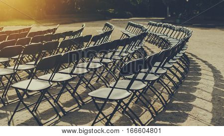 Empty seat rows of folding chairs on ground before a concert parallel and rounded arranged multiple black chairs on street on sunny day in park
