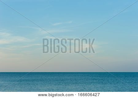 Calm Sea Ocean And Blue Sky BackgroundBeautiful white clouds on blue sky over calm sea with sunlight reflection
