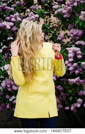 Blonde Girl Posing Against Blooming Violet Lilac Tree.