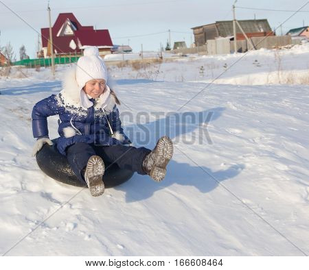 Cheerful girl on a snowy hill. The girl rolls down