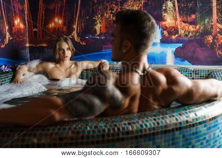 Sexy blonde sitting in luxurious jacuzzi. Young attractive tatooed man is looking at her close up shot from his back