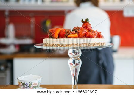 Close up of tasty cake with strawberry. Confectioner on background