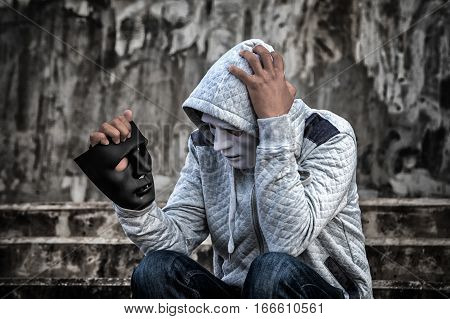 Asian Man In The Hood And White Mask With Confused Depression Sitting On Stairs And Looking At Black