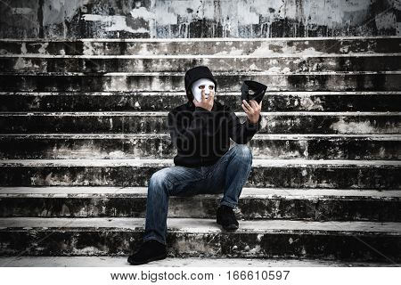 Asian man in the black hood and white mask with confused depression sitting on stairs and looking at black mask in scary abandoned building Human face expression Good and Bad temptation concept.