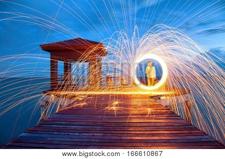 Hot Golden Sparks Flying from Man Spinning Burning Steel Wool on Wooden Bridge Extended into the Sea. Long Exposure Photography using Steel Wool Burning.