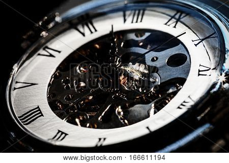 Close-Up of Luxury vintage mechanical watch with visible mechanism. In dark tone.