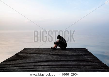 Frustrated Depression Man In The Hood Sitting On Wooden Bridge, Near The Beach On Sunset. Concept Of