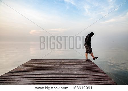 Suicide Concept., Depressed Young Man Wearing A Black Hoodie Standing On Wooden Bridge Extended Into