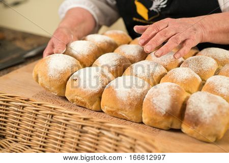 Baker's Hands On A Cluster Of Baked Bread Buns