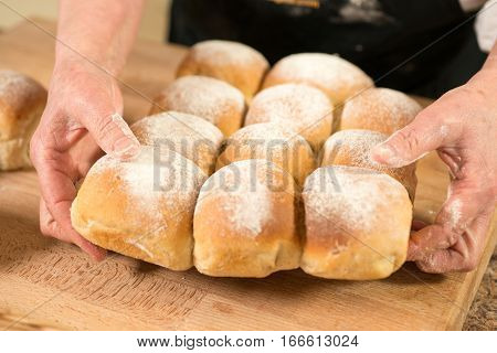 Hands Holding A Cluster Of Baked Bread Buns