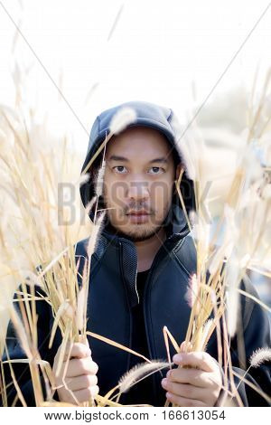 Mysterious Handsome Man In Black Hoodie Standing In The Grass Field.