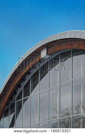 MINSK BELARUS - January 15 2017: Sports complex Olympic reserve. Pool National Olympic Training Center in athletics in Minsk Belarus. Element of building with circular shape facade against blue clear sky. Design of arched roof and stained glass system.