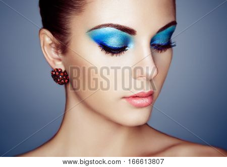 Portrait of young beautiful woman with blue makeup. Girl with earring close up. Fashion jewelry