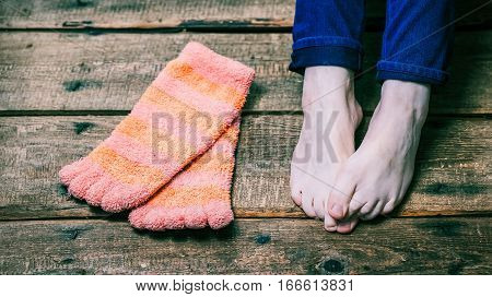 Bare female feet and funny glove socks laying on the wooden floor. Closeup view