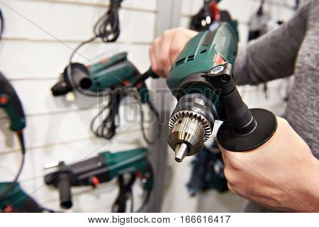 Man With Electrical Drill In Hardware Store