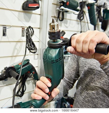 Man With Drill In Hardware Store