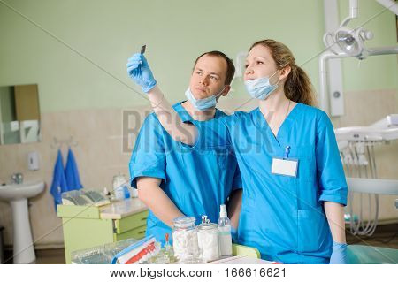 Female Dentist Showing X-ray To Male Colleague At Dental Clinic