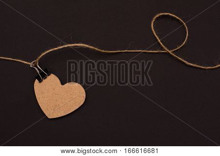 Heart Of Wood On A Rope With Clothespin On A Black Background