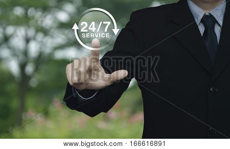 Businessman pressing button 24 hours service icon over blur flower and tree in park Full time service concept