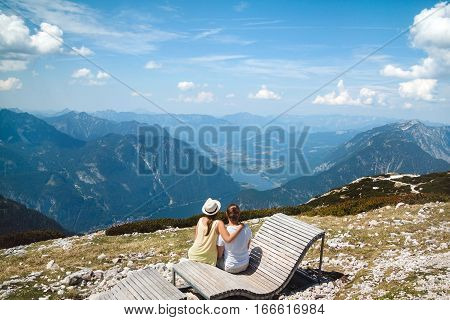 Couple relaxing on a chaise longue in mountains Dachstein Krippenstein in Austria